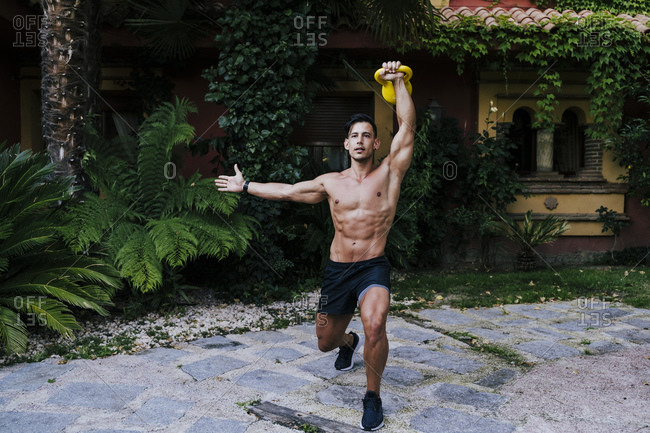 Shirtless man lifting kettlebell while standing against plants in yard