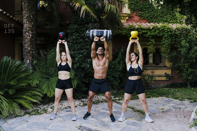 Male fitness instructor with women lifting weights while standing in yard