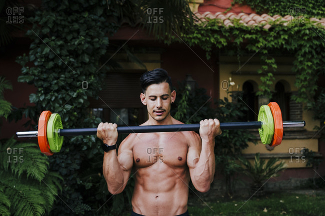 Shirtless mid adult man athlete lifting deadlift while standing in yard