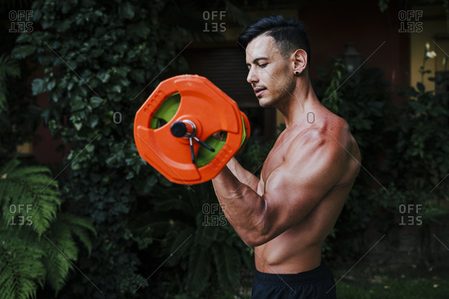 Shirtless male athlete lifting deadlift while standing in yard