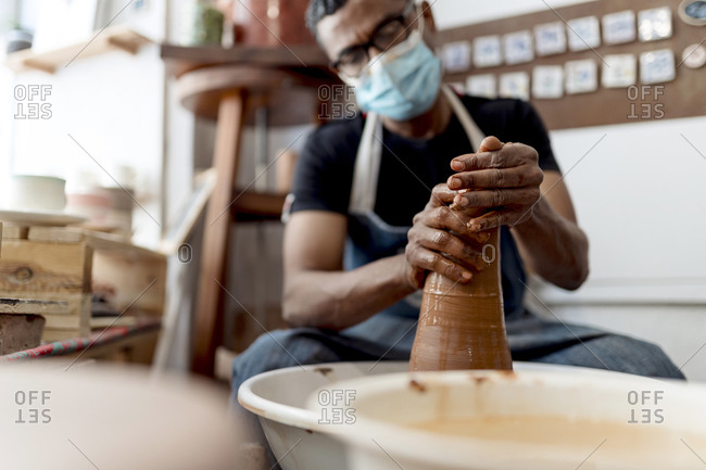 Male potter wearing mask molding shape to clay while sitting in workshop