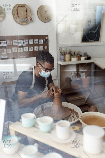 Male potter wearing mask molding shape to clay in workshop seen through window