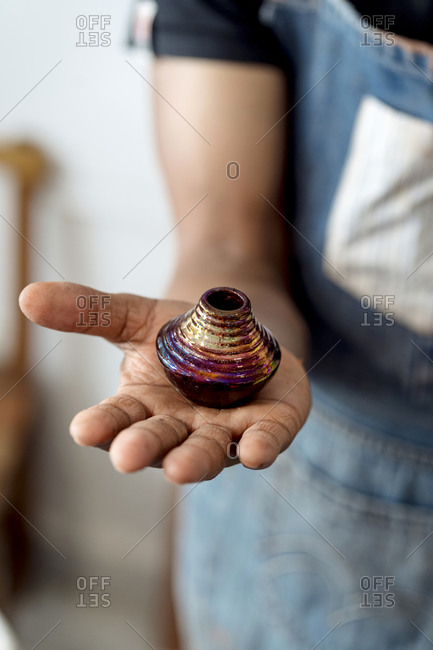 Close-up of male potter holding miniature vase in workshop