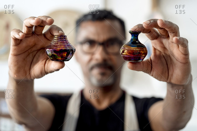 Close-up of male artist holding miniature vases in workshop