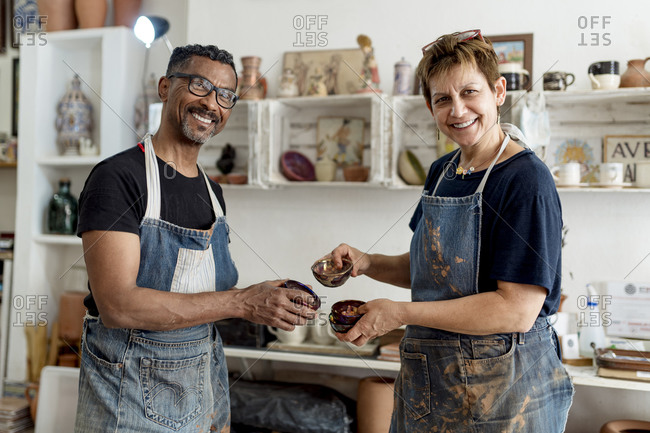 Smiling coworkers holding ceramics while standing in workshop
