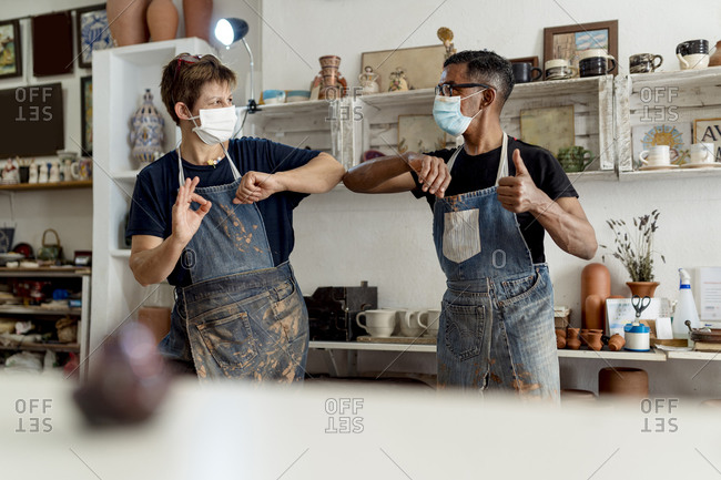 Coworkers wearing masks giving elbow bump while standing in workshop