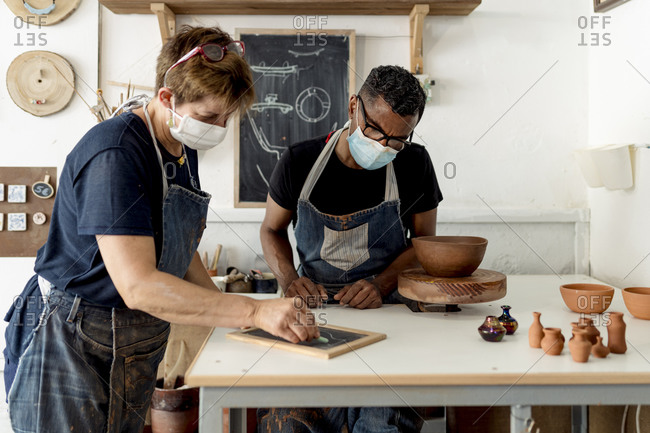 Coworkers wearing masks discussing designs over slate on table in workshop