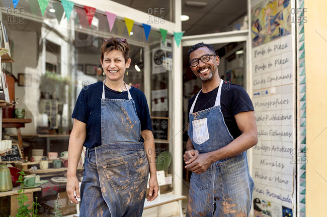 Smiling coworkers wearing aprons standing outside ceramic shop
