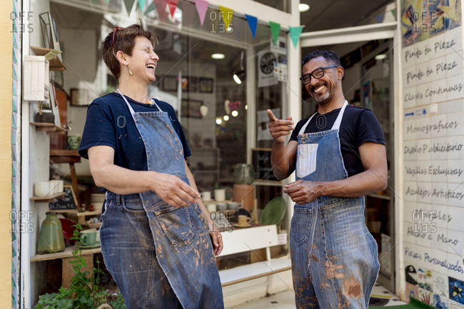 Cheerful coworkers talking while standing outside ceramic shop