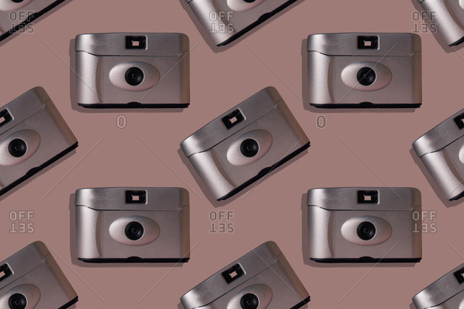 Close-up of retro cameras on pink background