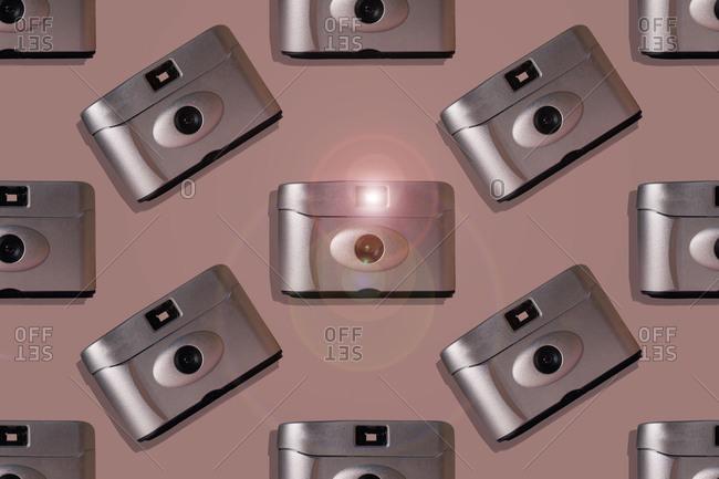 Retro cameras over pink background