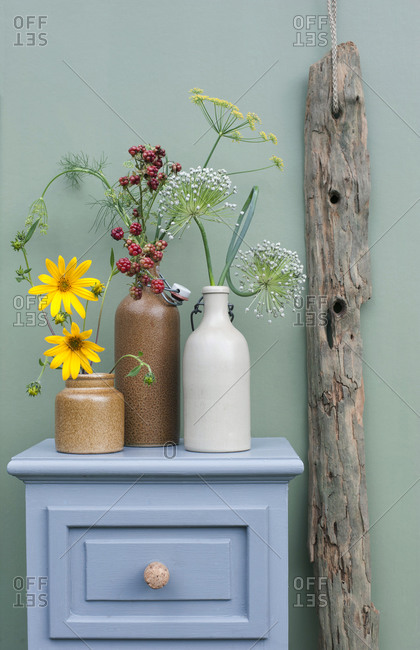 Drawer with DIY champagne cork handles- driftwood and flowers blooming in stoneware bottles