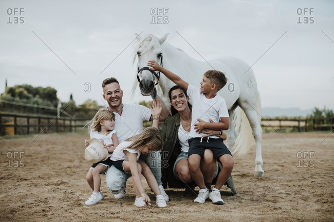 Cheerful parents with children crouching by horse in barn