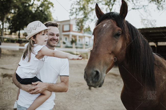 Father carrying daughter touching horse while standing outdoors