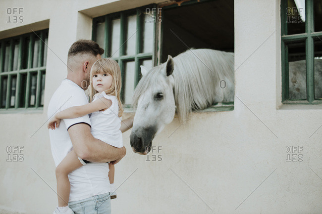 Father carrying cute daughter while stroking horse at stable