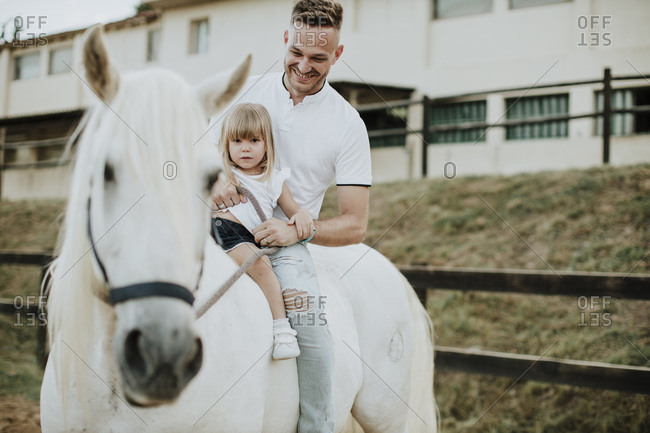 Smiling father with daughter riding horse
