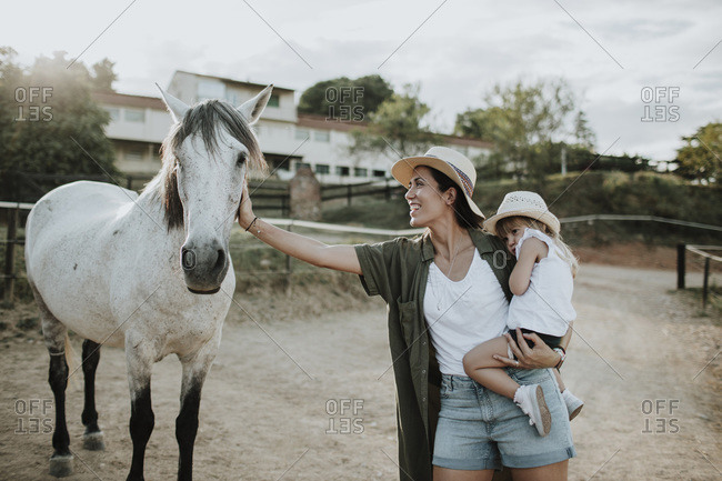 Mother carrying daughter stroking horse while standing on footpath