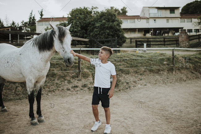Boy stroking white horse while standing in barn