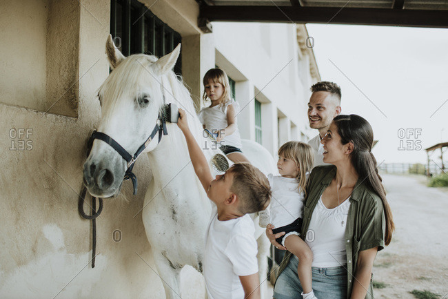 Parents looking at children brushing horse while standing outdoors