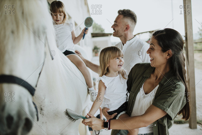 Parents with daughters brushing horse while standing outdoors
