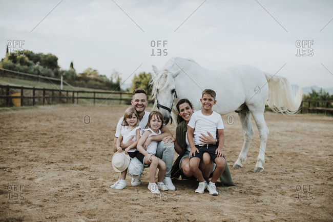 Cheerful family with horse in barn against sky