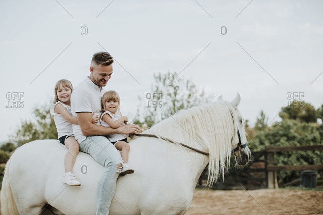 Father with daughters riding horse in barn against sky