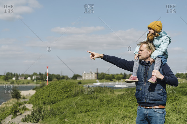 Father pointing at Rhine river while taking daughter on shoulder
