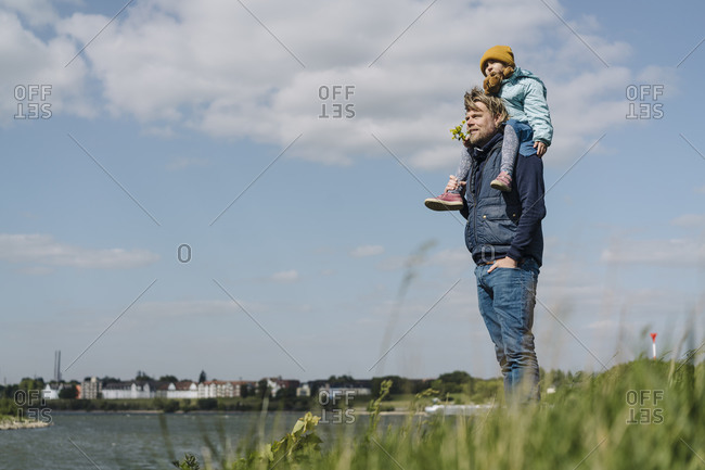 Father standing with hands in pockets while carrying daughter on shoulder near Rhine river