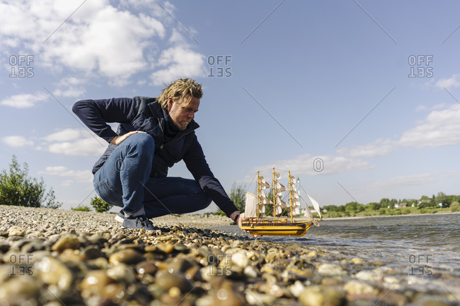 Man crouching while positioning toy boat on Rhine river
