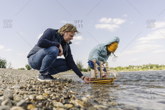 Father and daughter playing with toy boat near bank river