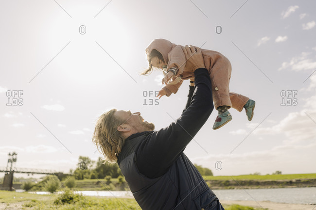 Father lifting baby daughter in air near river bank on sunny day