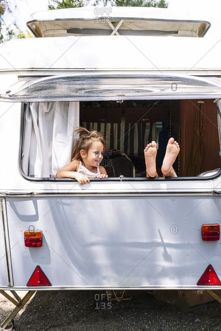 Girl looking at sister with foot on window in motor home