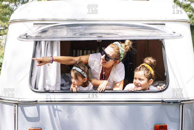 Cheerful woman with girls pointing through window of motor home