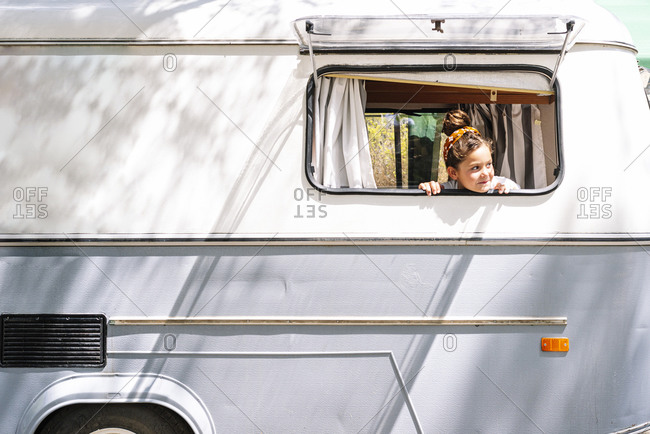 Girl looking through window while sitting in motor home