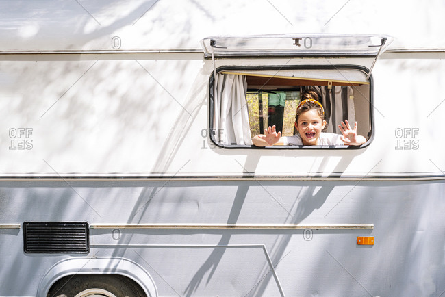 Cheerful girl screaming while looking through window of motor home
