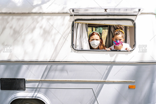 Mother and daughter wearing masks looking through window of motor home