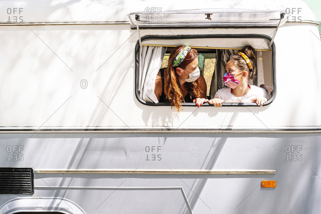 Mother and daughter wearing masks looking at each other in motor home seen through window