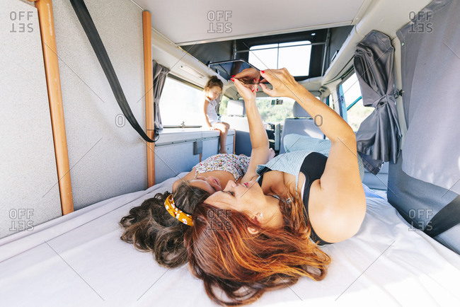 Mother and daughters using digital tablet while lying on bed in motor home