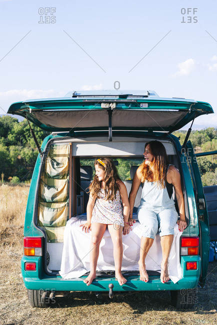 Mother and daughter looking away while sitting on bed in motor home