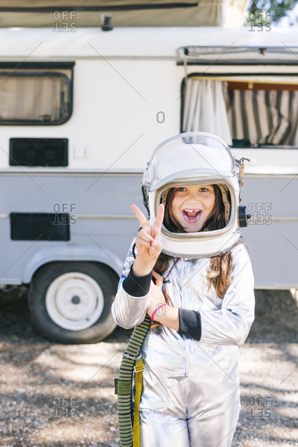 Girl wearing space suit showing peace sign while standing against motor home