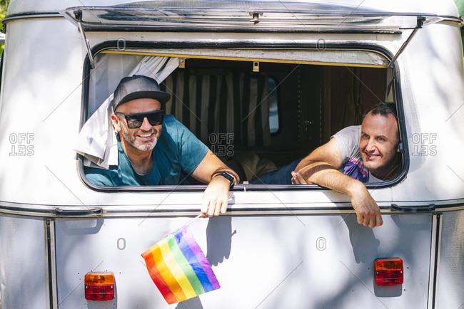 Smiling gay men sitting in motor home