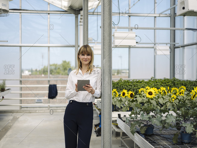 Smiling businesswoman using digital tablet while standing by plants in greenhouse