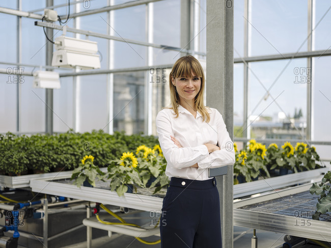 Confident businesswoman with arms crossed standing against plants in greenhouse
