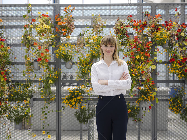 Smiling businesswoman with arms crossed standing against flowers in greenhouse