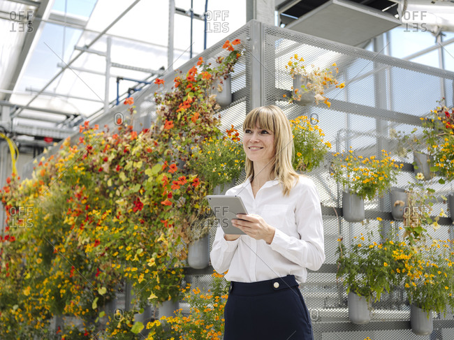 Smiling businesswoman using digital tablet while standing against flowers in greenhouse