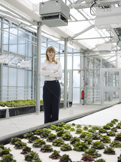 Female owner with arms crossed standing by plants growing in greenhouse