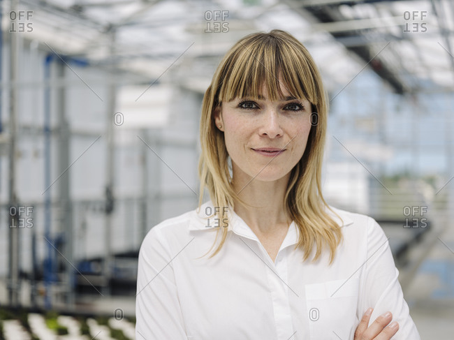 Close-up of confident businesswoman with blond hair standing in plant nursery