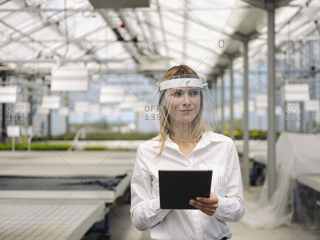 Businesswoman wearing face shield with digital tablet working in plant nursery