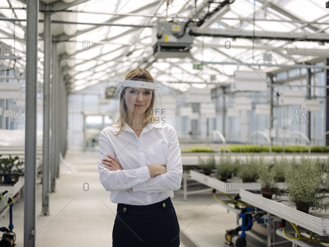 Businesswoman wearing face shield with arms crossed standing in greenhouse