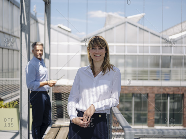 Smiling businesswoman with male coworker standing in greenhouse